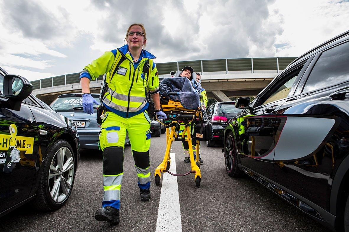 Eine Rettungssanitäterin die auf der Autobahn durch eine Rettungsgasse läuft