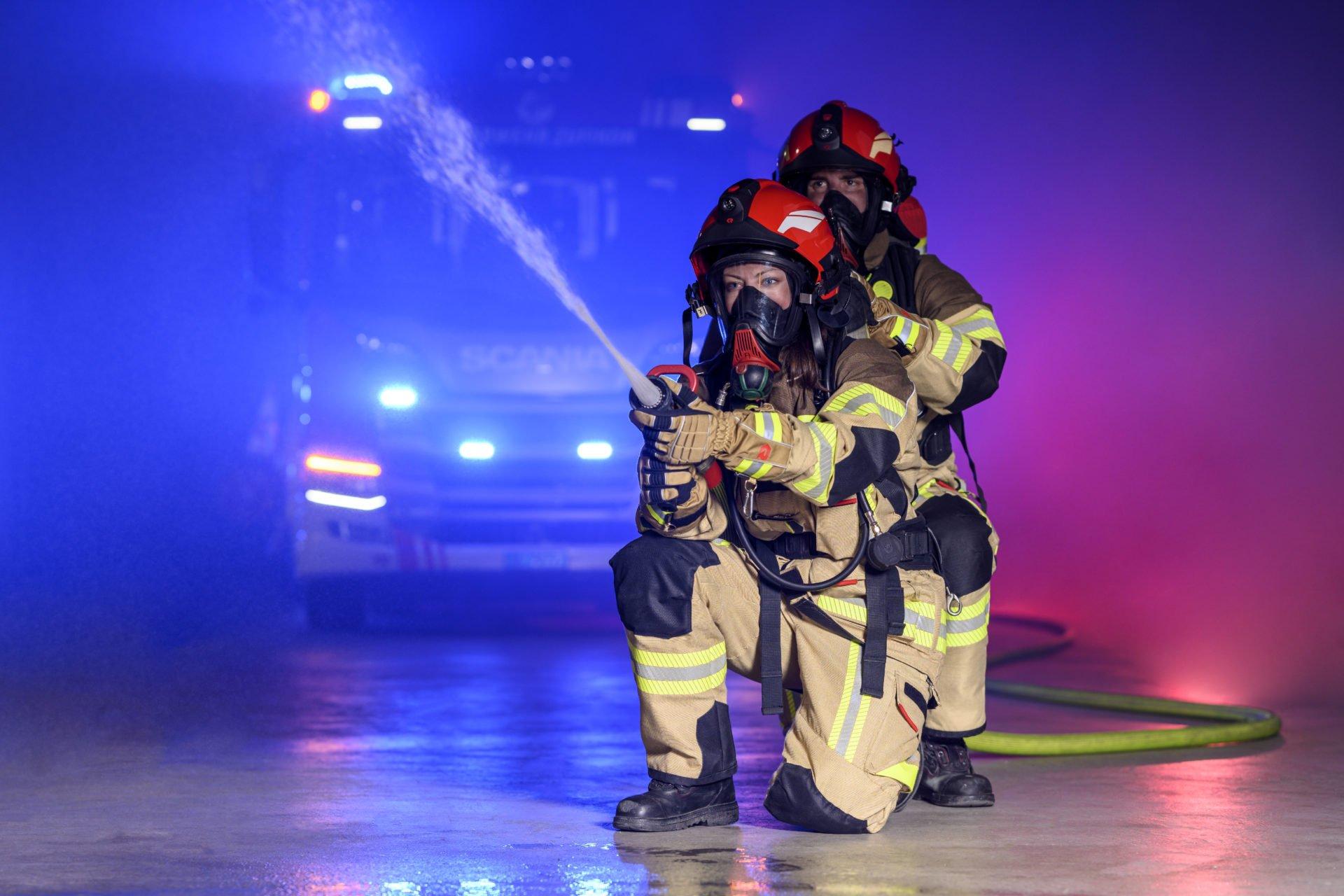 2 Feuerwehrmännder in Unfiform nd Feuerwehrschlauch